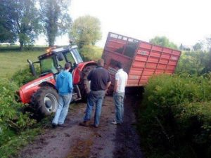 Three men looking at a tractor and trailer after a mishap